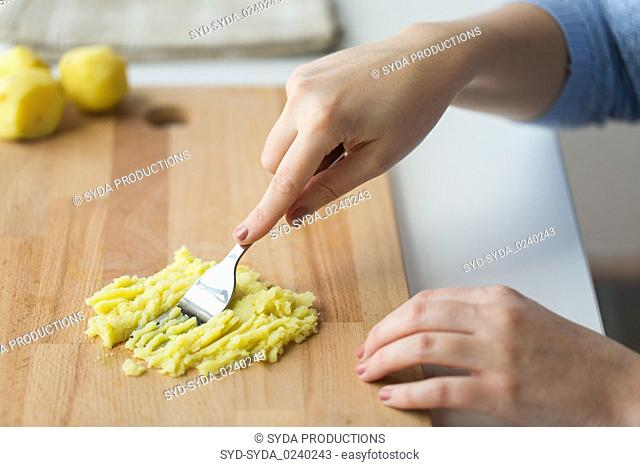 hand with fork making mashed potato on board