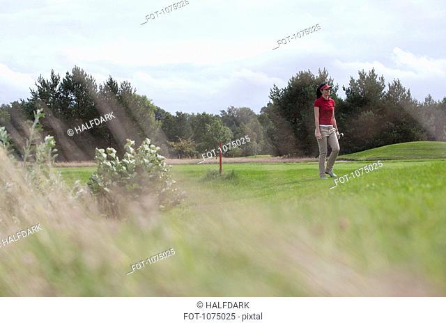 A female golfer walking on a golf course