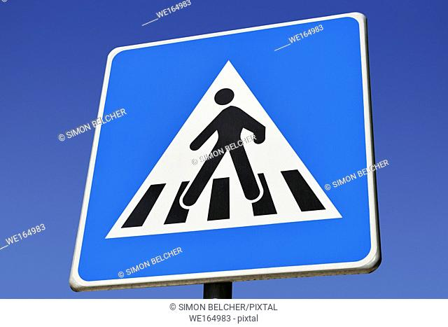 Pedestrian Crossing Sign Against a Blue Sky