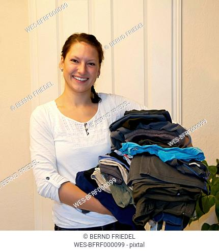 Germany, Brandenburg, Portrait of young woman with pile of laundry, smiling