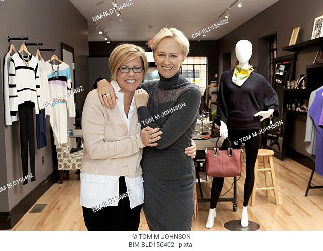 Caucasian small business owners working in clothing store