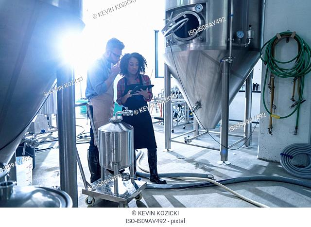 Colleagues in brewery by conical fermentation tank side by side looking at digital tablet