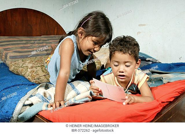 Guarani children sitting on the bed playing and reading in the poor area of Chacarita, Asuncion, Paraguay, South America