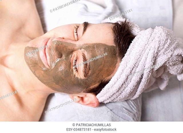 man with a brown mud mask on this face