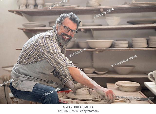 Portrait of male potter molding clay