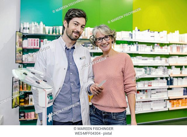 Portrait of smiling pharmacist with customer at sclaes in pharmacy