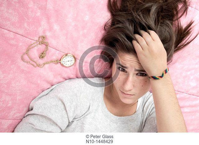 Teen girl lying next to a pocket watch