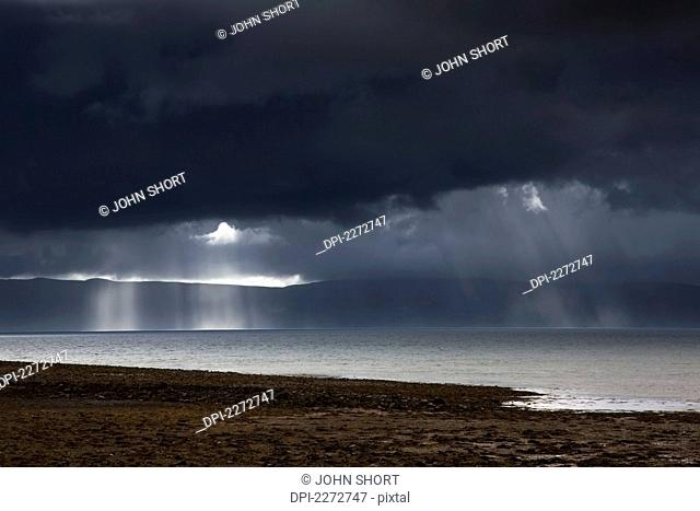 Sunbeams Shine Through Dark Storm Clouds Over The Water, Applecross Peninsula Highlands Scotland