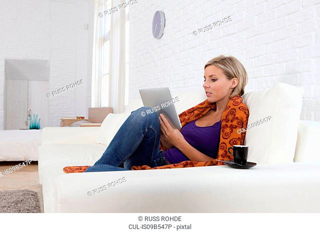 Mid adult woman sitting on sofa looking at digital tablet