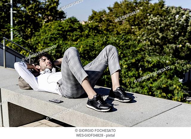 Young man lying on a bench outdoors relaxing