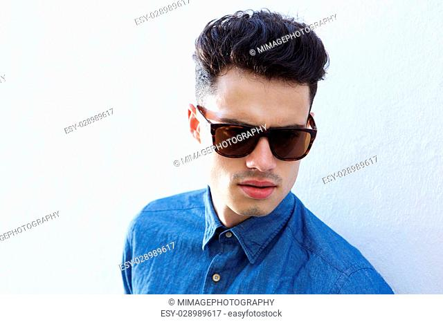 Close up portrait of a handsome male fashion model with sunglasses posing against white background