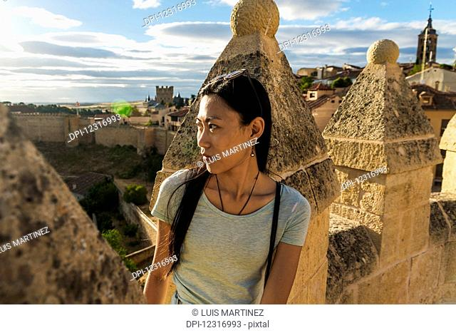 Asian girl sitting on the ancient walls of Segovia; Segovia, Castilla Leon, Spain
