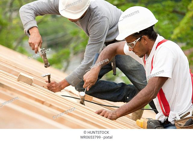 Hispanic carpenters using hammers on the roof of an under construction house