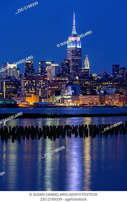 Empire State Building lights up to mark the Easter holiday in pastel fades colors, during the blue hour at twilight. The illuminated New York City skyline along...