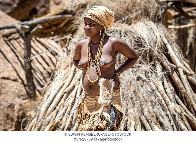 Damara woman stands by traditional dwellings at the Damara Living Museum, located north of Twyfelfontein in Namibia, Africa