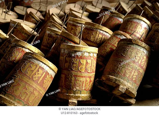 A cylinder containing or inscribed with prayers or litanies that is revolved on its axis in devotions, especially by Tibetan Buddhists