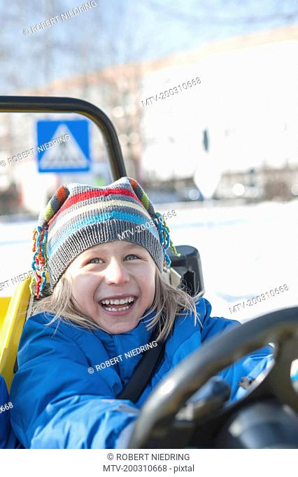 Boy driving electric toy car