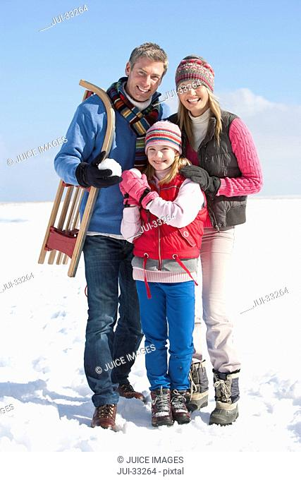 Portrait of smiling parents and daughter with snowball and sled in snow