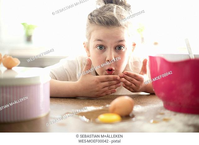 Portrait of embarrassed little girl in the kitchen