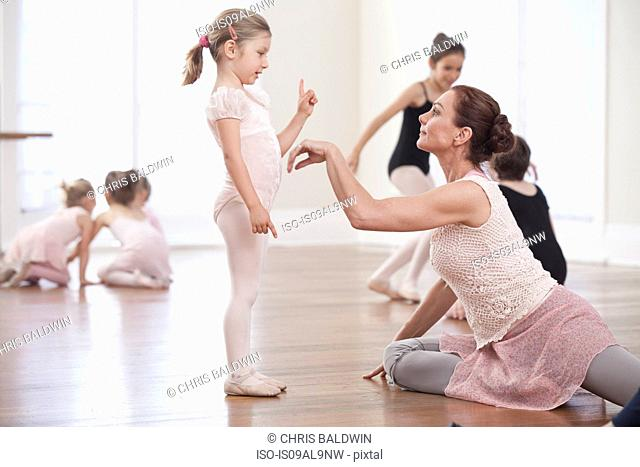 Teacher demonstrating to girl in ballet school