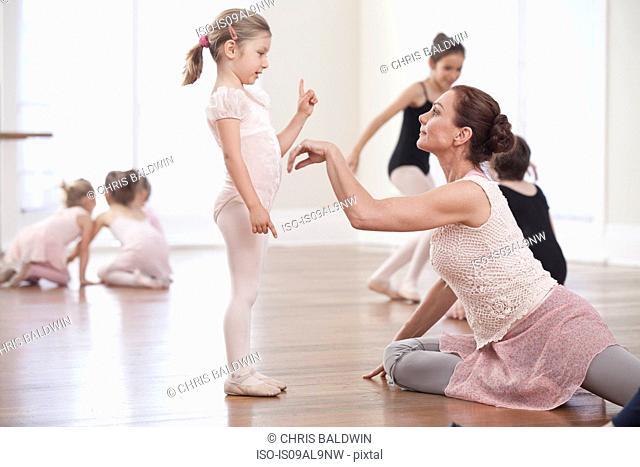 Teacher demonstrating to girl in ballet school