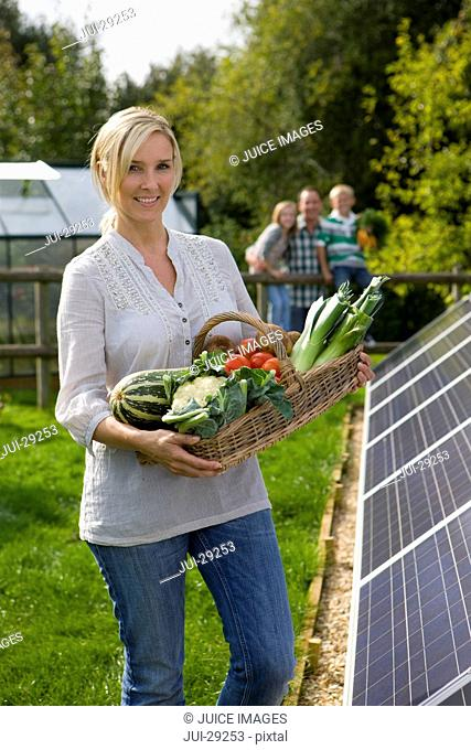 Woman holding basket of vegetables near large solar panels with family in background