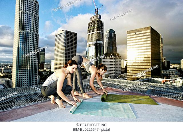 Caucasian women rolling exercise mats on urban rooftop after yoga