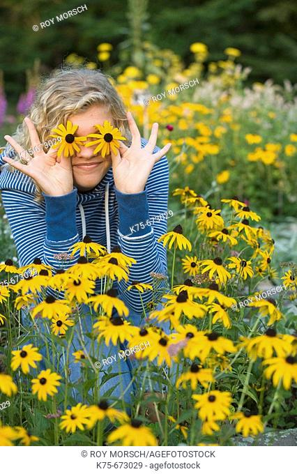 Teen holding wildflowers on her eyes