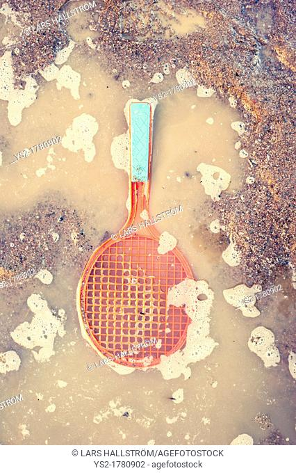 Plastic toy tennis racket lying in water puddle