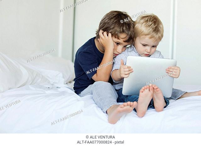 Young brothers sitting on bed looking at digital tablet