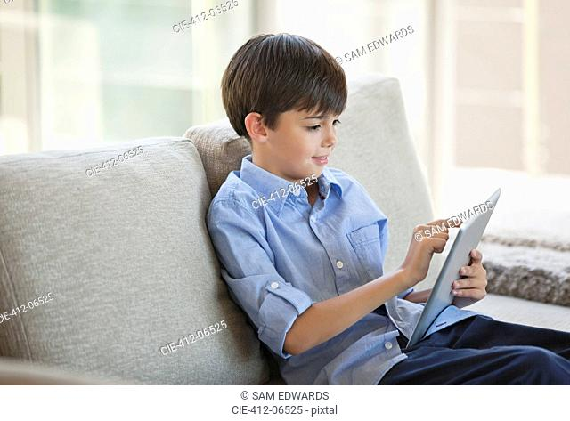 Boy using tablet computer on sofa