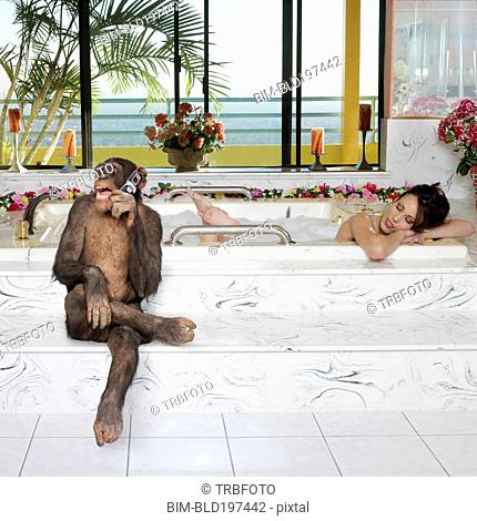 Monkey talking on cell phone while woman takes a bath
