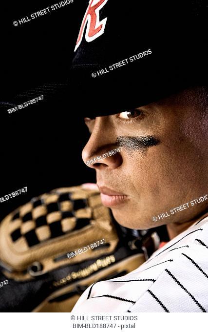 Frowning mixed race baseball player
