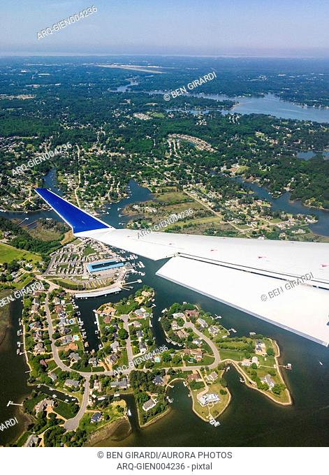 Wing of airplane during flight over lakeside houses, Poquoson, Virginia, USA