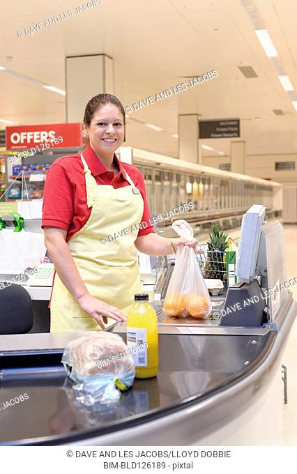 Hispanic woman working at grocery checkout