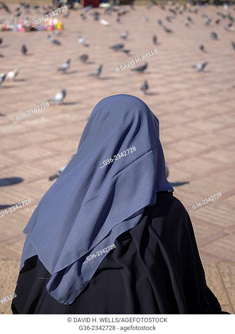 Rear view of Arab woman with pigeons on street in Casablanca, Morocco