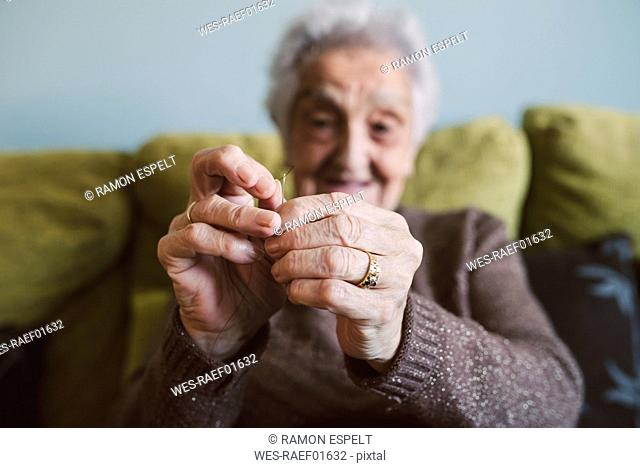Hands of senior woman sitting on couch passing thread through buttonhole of sewing needle