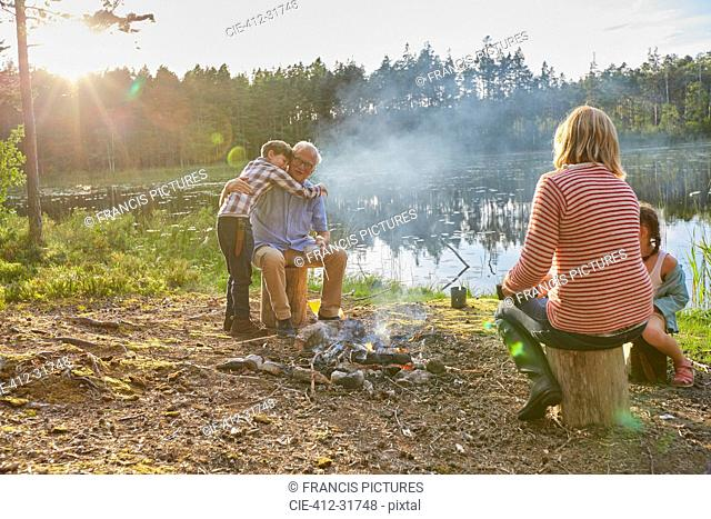 Grandparents and grandchildren hugging at campfire at sunny lakeside