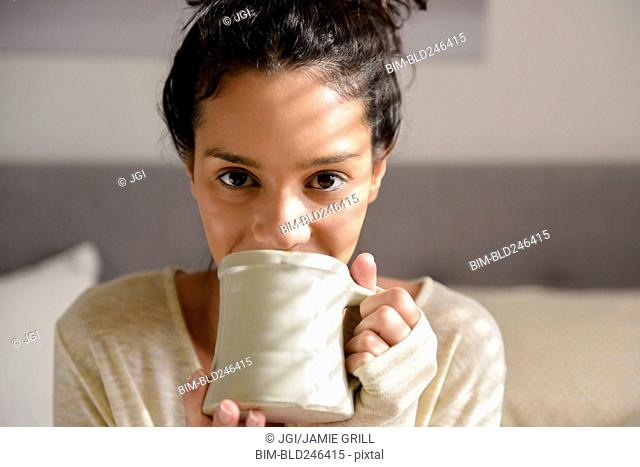 Hispanic woman drinking coffee