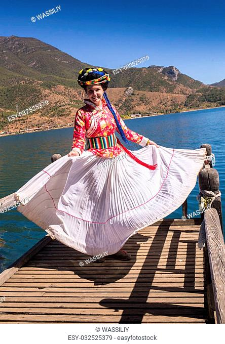 The girl in national dress on the lake in the China