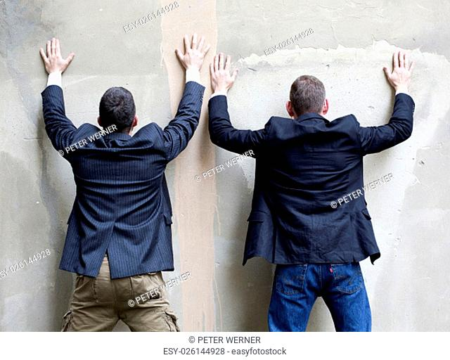 two men in jackets standing against a wall