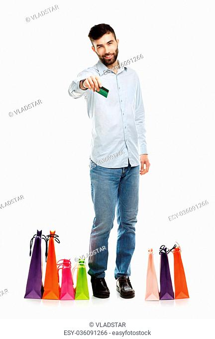Handsome smiling man with shopping bags and holding credit card. Christmas and holidays concept