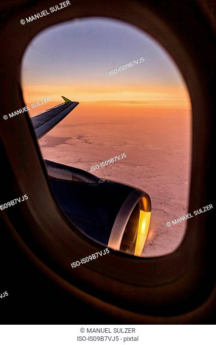 Sunset cloudscape and airplane wing through airplane window