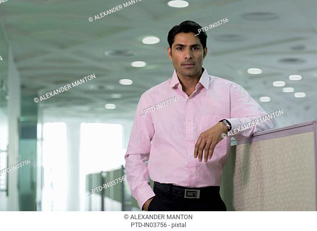 Businessman leaning on partition in office