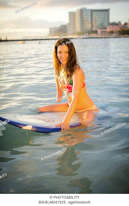 Mixed race amputee sitting on surfboard in ocean
