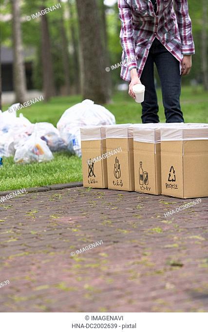 Woman Trowing Garbage into a Dust Bin
