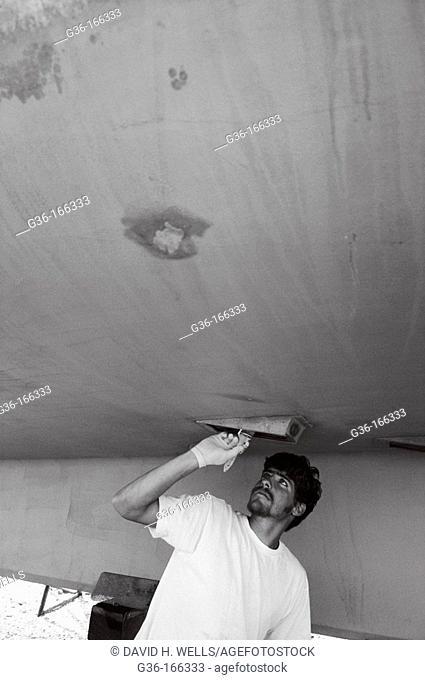 Fisherman painting boat hull