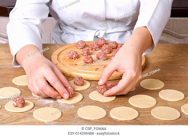Cook hands lay out minced meat on dumplings