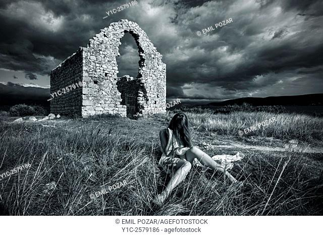 Young woman before derelict stone building Black & White retro