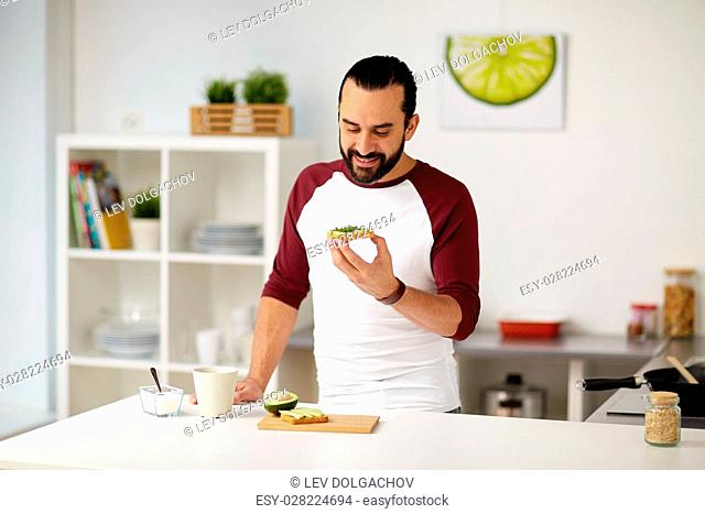 vegetarian food, healthy eating, people and diet concept - man having avocado sandwiches for breakfast at home kitchen